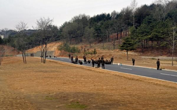 Les soldats s'activent pour embellir la route qu'utilisera le convoi des officiels
